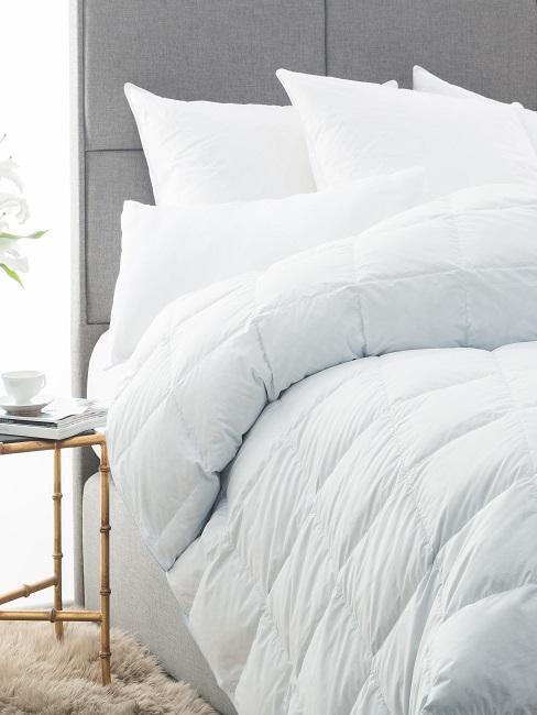 Weiße Bettdecke im Bett mit weißen Kissen.