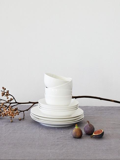 Tisch mit einem Geschirr-Set in Weiß, Feigen und einem Zweig