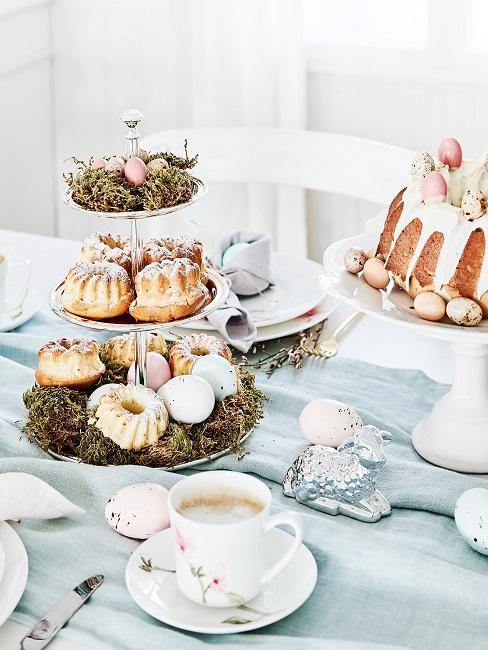 Gedeckter Tisch mit Kaffee und Kuchen sowie einem osterlich dekoriertem Etagere mit kleinern Eiern und Moos