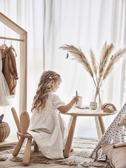 Design Kinderzimmer mit Mädchen auf Stuhl, das auf kleinem Holztisch malt