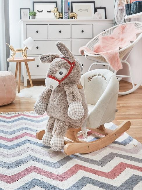 Bunter Teppich im Kinderzimmer mit einem Schaukelstuhl für Kinder und einem Kuscheltier Esel darauf sitzend