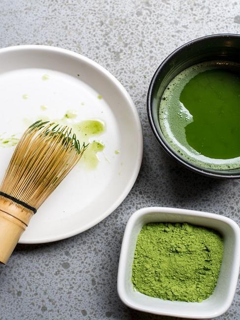 Teezeremonie Matchapulver in Schale neben Bambusbesen