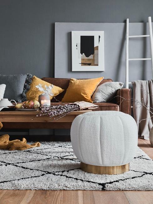Wohnzimmer mit grauer Wandfarbe, braunem Sofa und hellen Wohnaccessoires