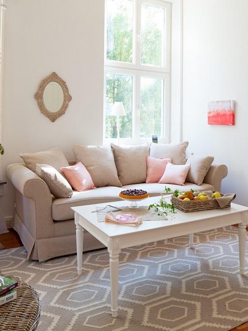 Mesa de madera blanca sobre alfombra geométrica blanca y salmón y sofá mullido marrón claro con cojines marrón claro y rosas
