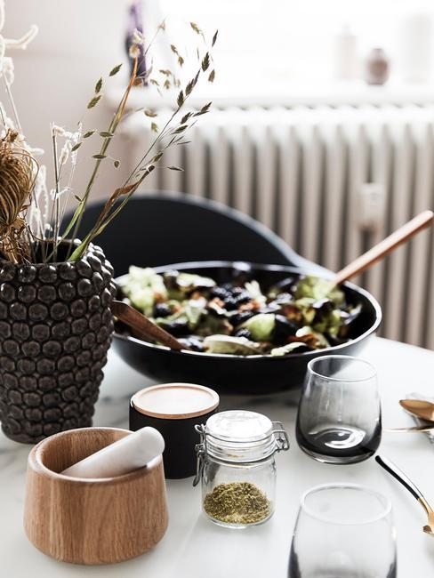 Comida con platos y jarrones negros y utensilios marrones