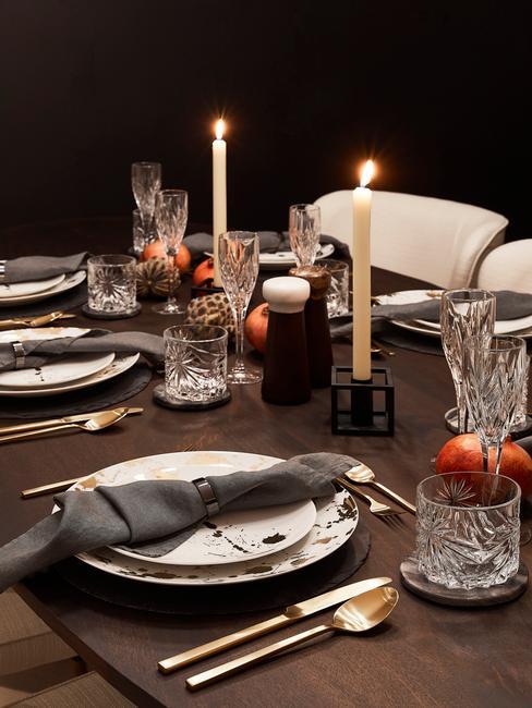 Mesa de madera preparada para la cena con vajilla y velas