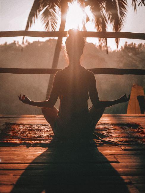 Mujer practicando meditación durante el atardecer