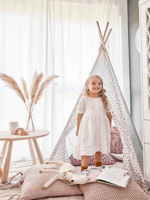 Niña pequeña en su habitación con una tienda tipi