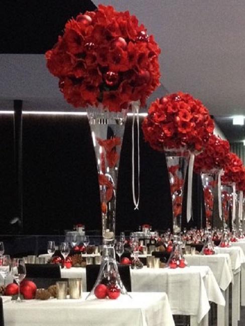 ramos de rosas rojas en jarrones de cristal altos como decoración de mesas de boda
