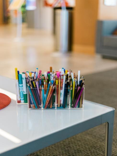 Pupitre con recipiente de cristal que contiene muchos lápices de todos los colores