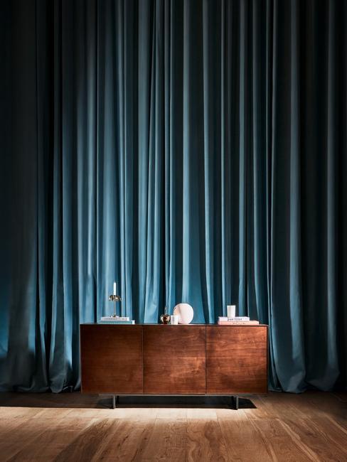 Commode en bois devant un très grand rideau bleu turquoise