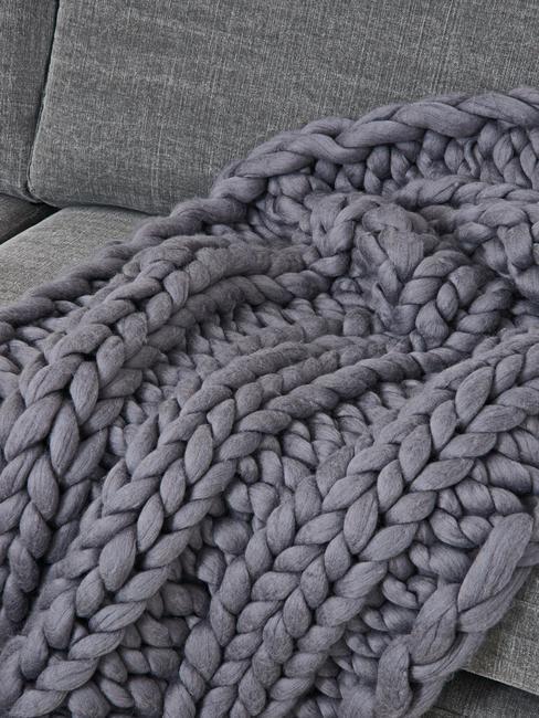 Couverture gris anthracite sur un canapé gris clair