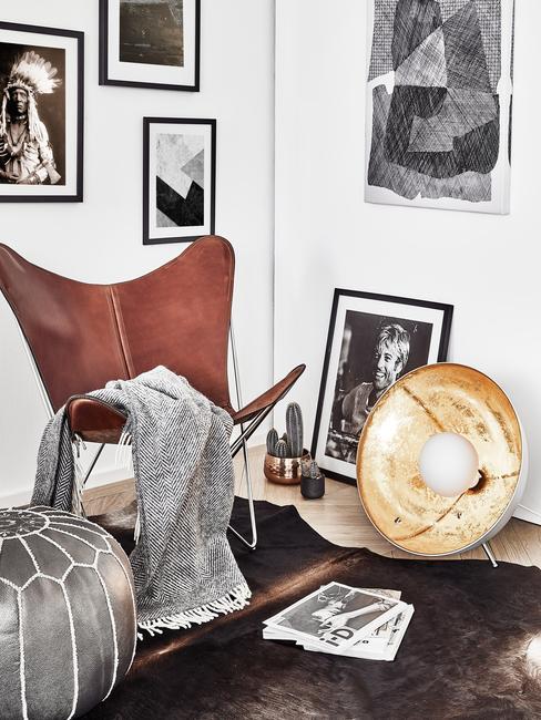 Coin salon avec fauteuil et pouf en cuir ainsi que des photos encadrées sur des murs derrière
