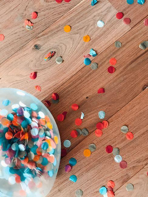 Confettis de toutes les couleurs éparpillés sur une table en bois et à l'intérieur d'un bocal en verre