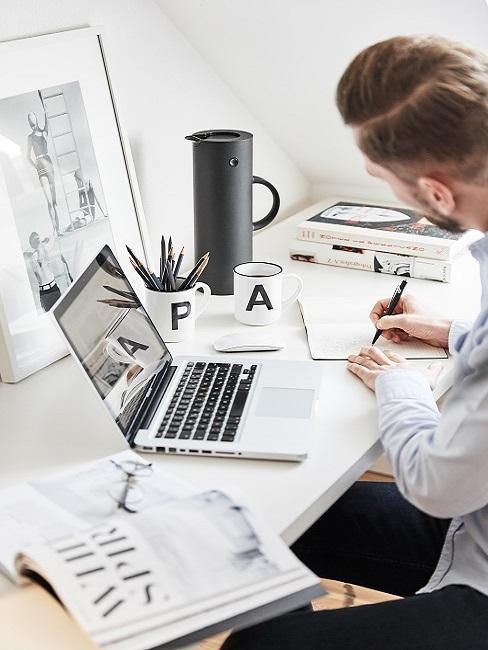 Homme au bureau avec un ordinateur portable et un vision board derrière
