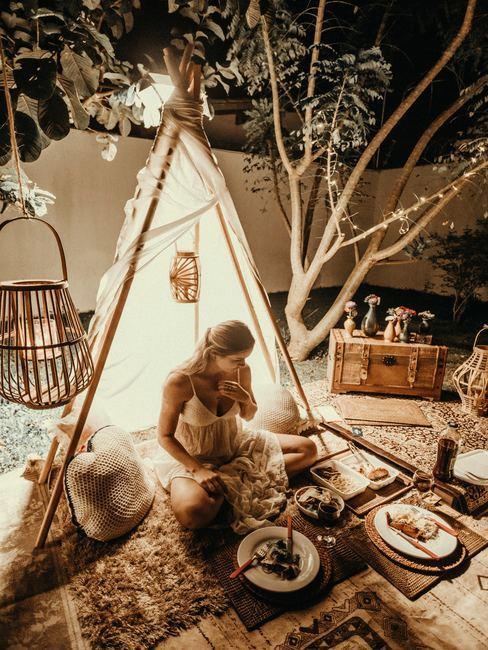 Femme assise dans un décore enchanteur bougies et repas