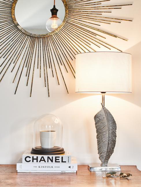 Lampa stojąca na komodzie obok książek i świeczki pod metalową dekoracją ścienną