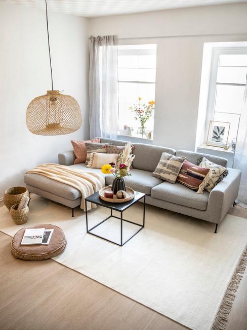 Jasny salon z kremowym dywanem, szarą kanapą, modernistycznym stolikiem na kawę oraz dekoracjami