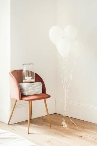 Białe pomieszczenie z krzesłem, na którym są książki oraz balony