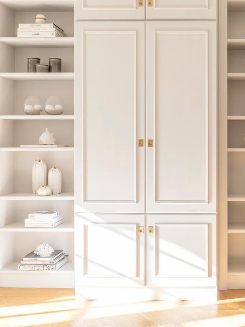 Biała szafa na ubrania, obok której stoi szafka z półkami i dekoracjami