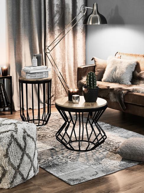 Ciemno urządzony salon z kanapą, pufem, dywanem, stojącą lampą oraz stolikiem do kawy