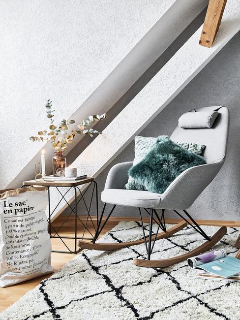 Szary fotel na biegunach, prz którym na podłodze leżą książki