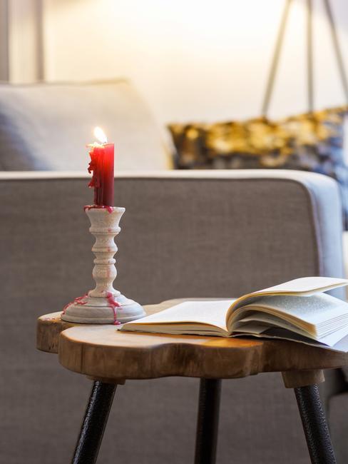 Drewniany stolik pomocniczy z książką i palącą się świecą.