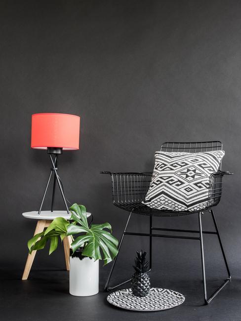 Wnętrze z czerną ścianą, foletem z biało-czarną poduszką, rośliną oraz czerwoną lampą