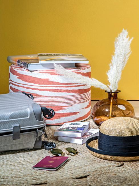 Żółte pomieszczenie z walizką, słomkowym kapeluszem oraz koszem