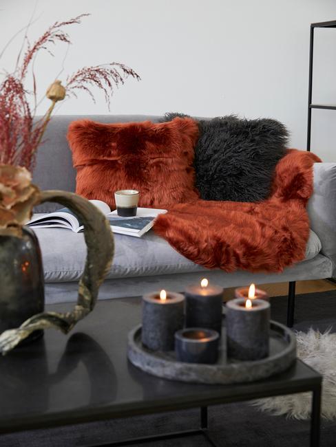 Szara sofa przy niej czarny stolik kawowy. Dodatki w rudawych odcieniach
