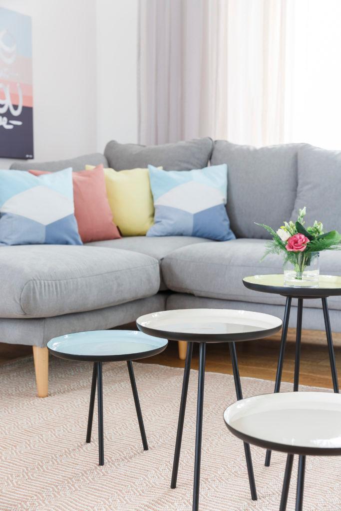 Szary salon z szarą kanapą, kolorowymi poduszkami dekoracyjnymi oraz stolikami kawowymi