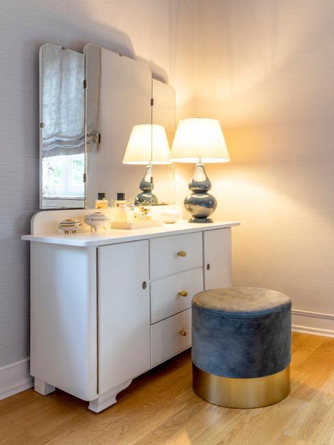Biała komoda z lampą oraz szarym pufem