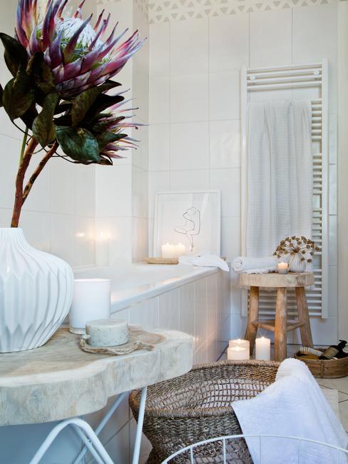 Fragment łazienki z wanną, drewnianym stolikiem oraz marmurowym stolikiem z kwiatami i świecami