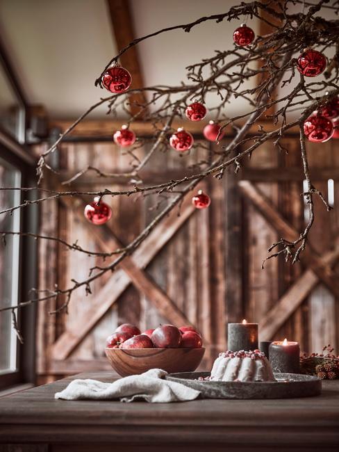 Drewniany stół, nad którym znajduje się udekorowana czerwonymi bombkami gałęź