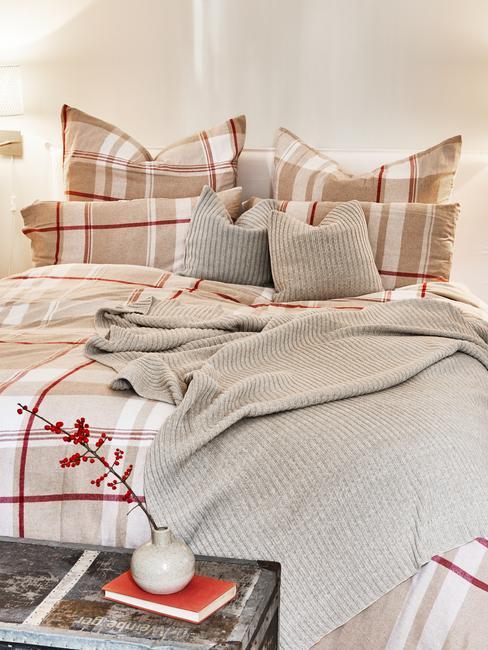 Przytulna sypialnia z pościelą w beżowo-czerwoną kratę