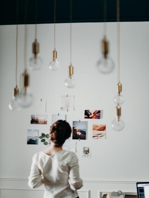 Dziewczyna stojąca przed ścianią ze zdjęciami oraz wiszącymi żarówkami