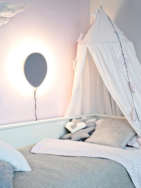 Łóżko z baldachimem oraz szarą lampą na ścianie w kształcie balona