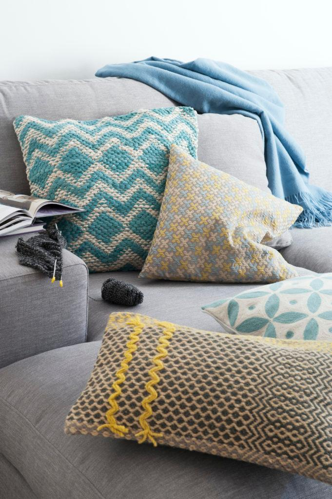 Zbliżenie na szara kanapę z niebieskimi poduszkami dekoracyjnymi oraz kocem