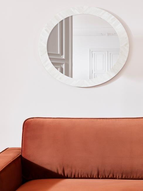 Lustro piszące nad pomarańczową kanapą