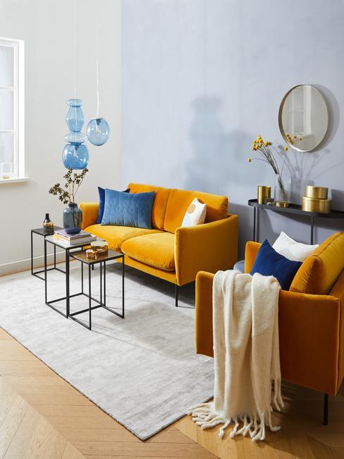 Salon z niebieskimi ścianmi, musztardową kanapą oraz fotelem, białym dywanem i stolikiem na kawę