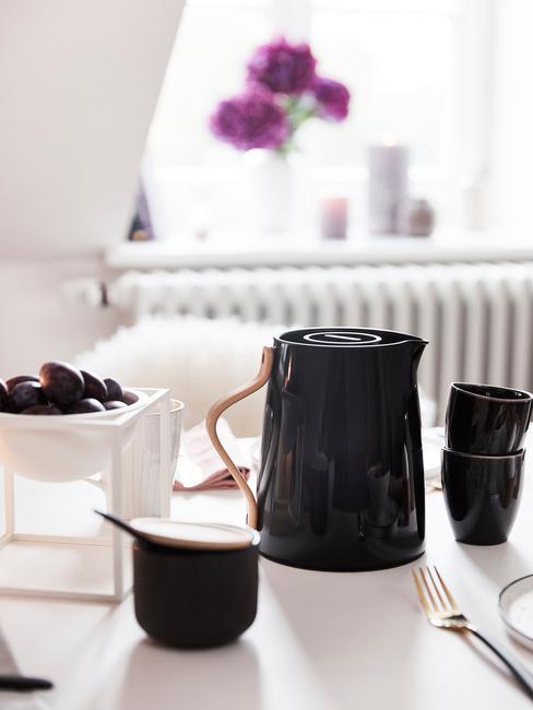 Zbliżenie na stolik z czarnym czajnikiem do herbaty oraz szklankami
