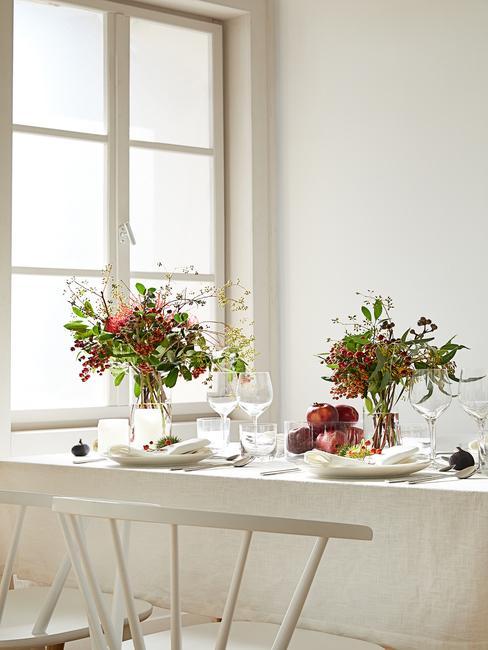 Stół stojący przy oknie z wazonami z kwiatami
