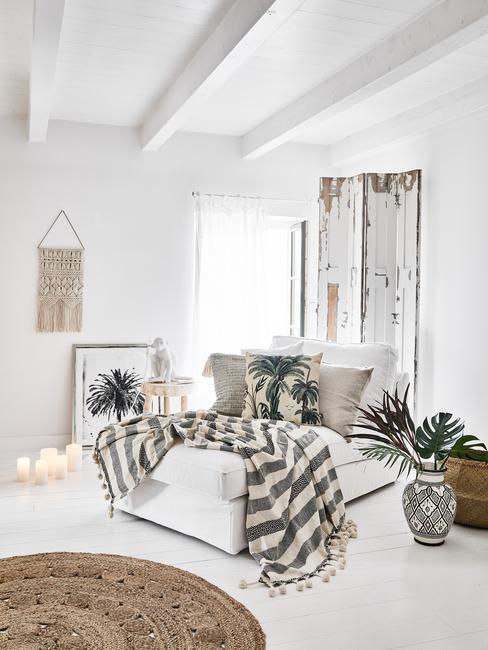 Sypialnia z białym łożkiem, narzutą w paski, roślinami w wazonach oraz makramą na ścianie