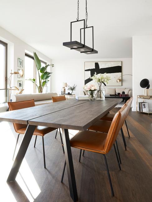 Jadania z drewnianym stołem, skórzanymi krzesłami oraz czarnymi dodatkami