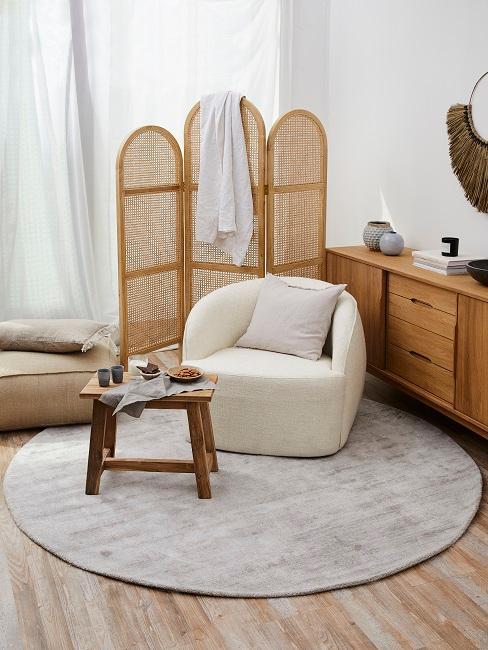 Sessel vor Raumteiler auf rundem Teppich