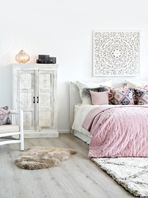 Biała sypialnia w stylu boho, z szafką na ubrania oraz dekoracją na ścianie