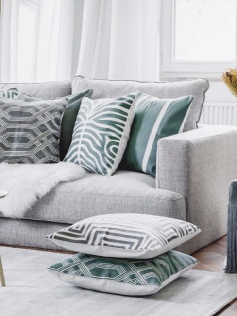 Wohnzimmer in grau mit salbeigrünen Akzenten in form von gemusterten salbeigrünen Kissen und einem Fransen Hocker mit Blumendeko
