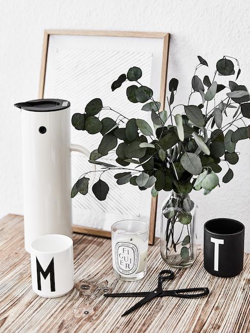 Jarrón con plantas y tazas con letras