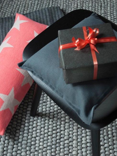 regalo envuelto en papel negro sobre una silla negra y con un lazo decorativo
