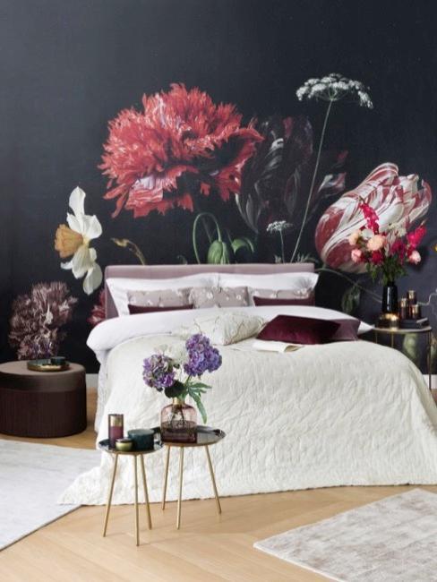 Donker behang met bloemmotief in slaapkamer met bed, decoratieve elementen en accessoires